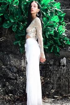 Portret pięknej kobiety rasy kaukaskiej o ciemnych długich włosach w szerokich nogawkach klasycznych spodniach pozowanie w pobliżu skał i zielonych liści tropikalnych egzotycznych tła