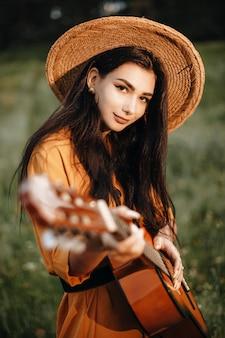 Portret pięknej kobiety rasy kaukaskiej z ciemnymi długimi włosami patrząc na kamery uśmiechając się z gitarą w dłoniach na sobie kapelusz na zewnątrz w przyrodzie.