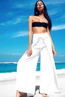 Portret pięknej kobiety rasy kaukaskiej z ciemnymi długimi włosami w klasycznych szerokich nogawkach pozowanie na letniej plaży z białym piaskiem na niebieskim niebie i oceanie
