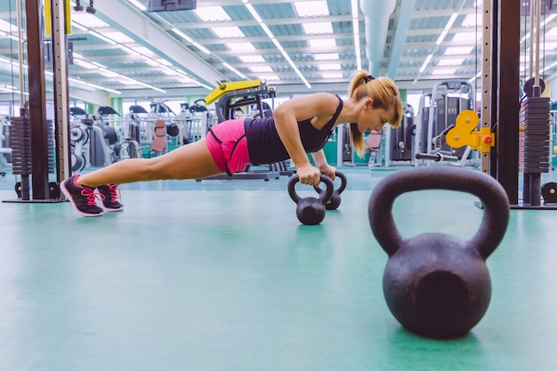 Portret pięknej kobiety robi pompki nad czarnymi żelaznymi kettlebells w treningu crossfit na centrum fitness