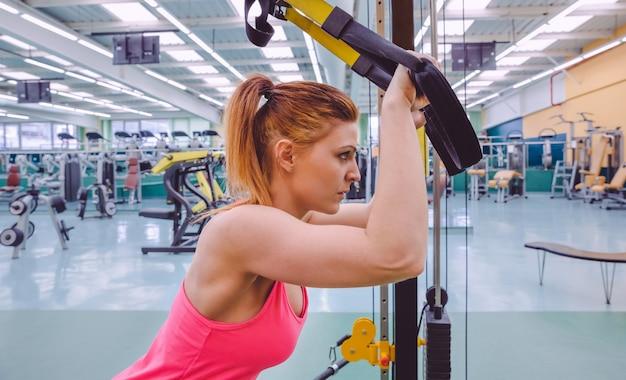 Portret pięknej kobiety robi twardy trening zawieszenia z pasami fitness w centrum fitness. koncepcja zdrowego i sportowego stylu życia.