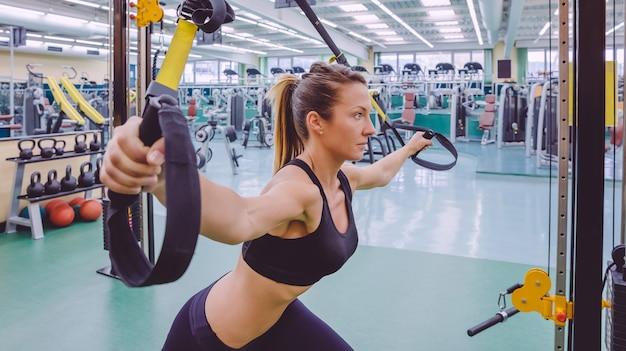 Portret pięknej kobiety robi twardy trening zawieszenia z paskami fitness w centrum fitness. koncepcja zdrowego i sportowego stylu życia.