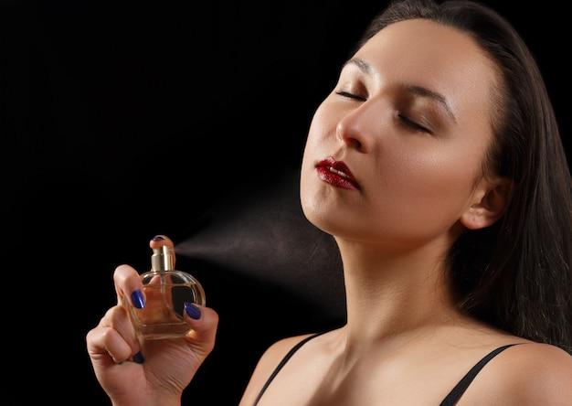 Portret pięknej kobiety rozpylania perfum. na czarno