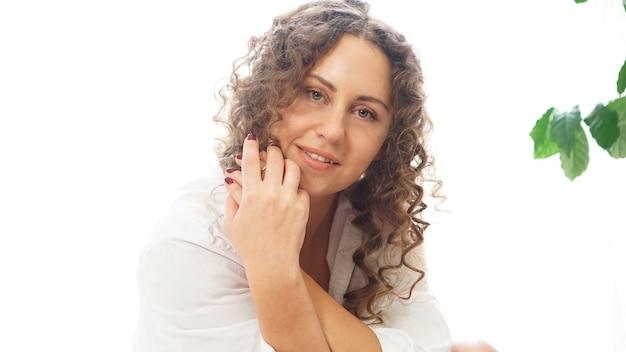Portret pięknej kobiety siedzącej w domu z roślinami i uśmiechając się do kamery