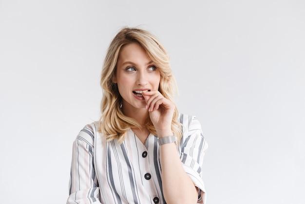 Portret pięknej kobiety słodkie 20s na sobie ubranie, myśląc i patrząc na bok na copyspace na białym tle nad białą ścianą