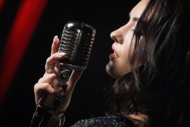 Portret pięknej kobiety śpiewa w mikrofonie