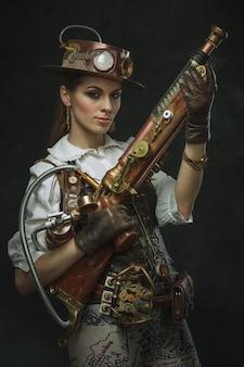 Portret pięknej kobiety steampunk trzyma broń