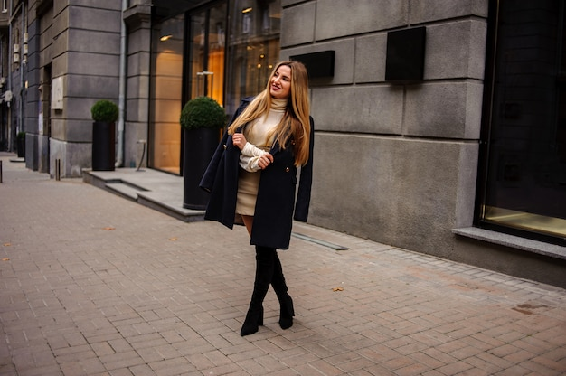 Portret pięknej kobiety stojącej na chodniku w beżowej sukience i czarnym płaszczu