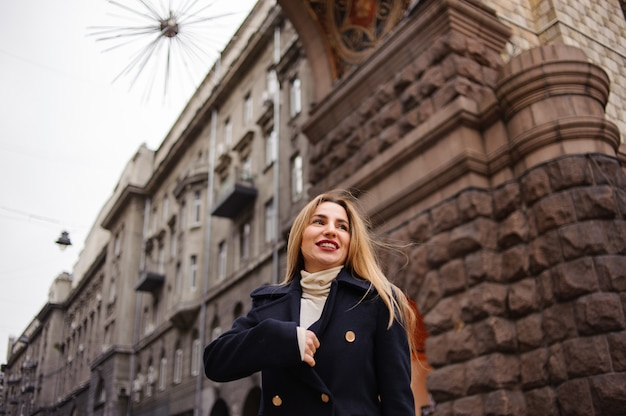 Portret pięknej kobiety stojącej na środku miasta w czasie jesieni