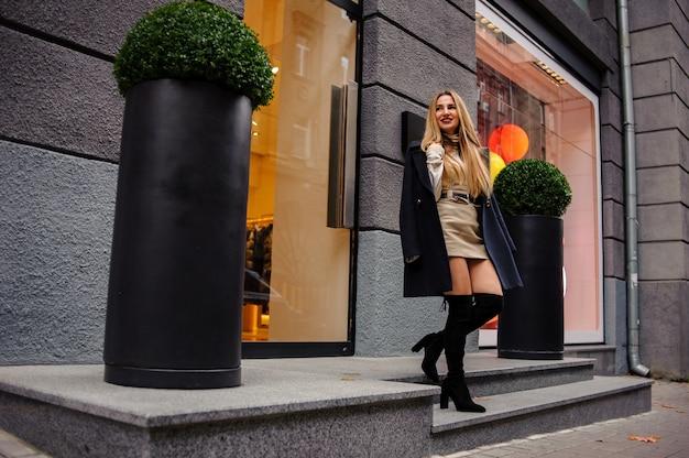 Portret pięknej kobiety stojącej w pobliżu sklepu w beżowej sukience i czarnym płaszczu