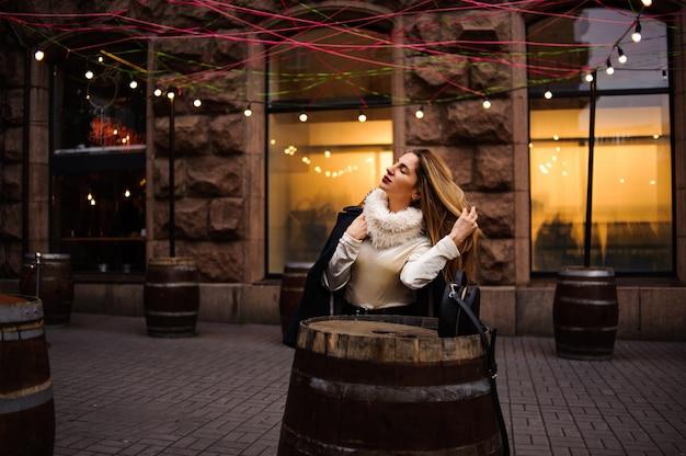 Portret pięknej kobiety stojącej w pobliżu stołów beczkowych w beżowej sukience i czarnym płaszczu