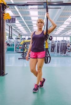 Portret pięknej kobiety stojącej z pasami fitness w centrum fitness. koncepcja zdrowego i sportowego stylu życia.