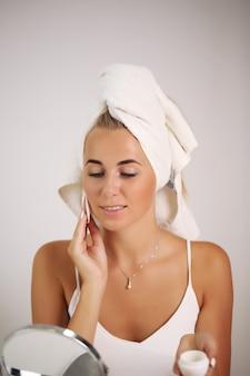 Portret pięknej kobiety stosowania kremu do pielęgnacji skóry