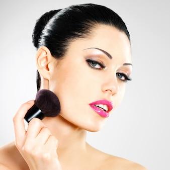 Portret pięknej kobiety stosując róż na twarzy za pomocą pędzelka kosmetycznego