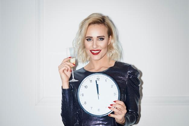 Portret pięknej kobiety trzymającej szampana i zegar