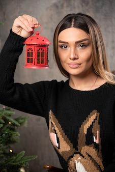 Portret pięknej kobiety trzymającej zabawki boże narodzenie altana. wysokiej jakości zdjęcie