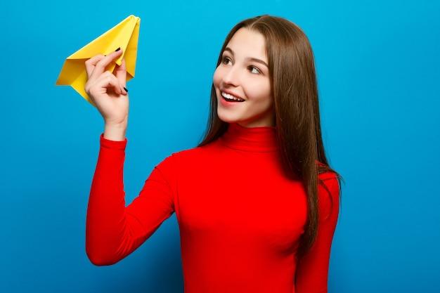 Portret pięknej kobiety trzymającej żółty papierowy samolot. na niebieskim tle.