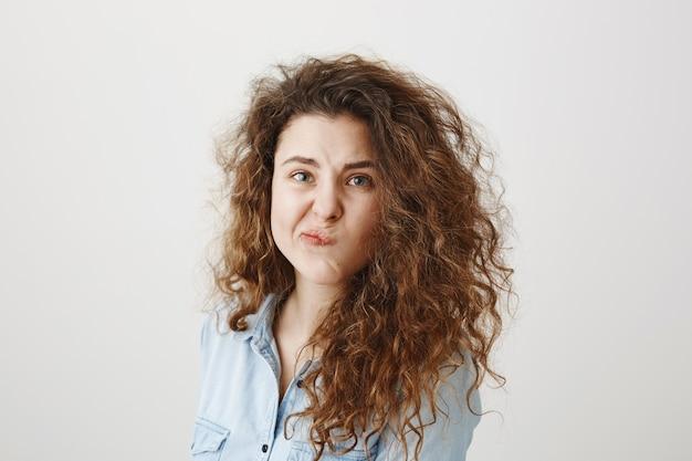 Portret pięknej kobiety twarz z bliska portret młode kręcone włosy studio na szaro