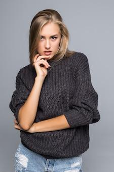 Portret pięknej kobiety ubrana w ciepły sweter z dzianiny na jej ciele na szarym tle na białym tle