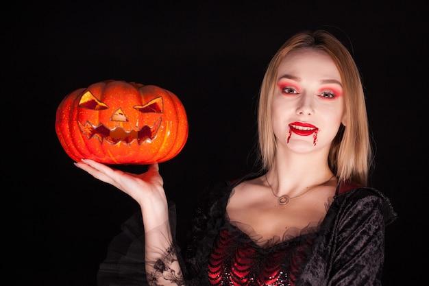 Portret pięknej kobiety ubranej jak wampir z zakrwawionymi ustami trzyma dynię na czarnym tle.