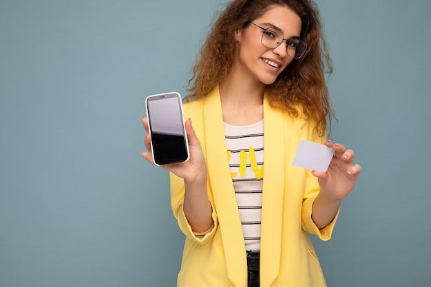 Portret pięknej kobiety ubranej w żółtą kurtkę i okulary optyczne izolowane na tle ściany trzymającej i pokazującej telefon z pustym ekranem i kartą kredytową, patrząc na kamerę