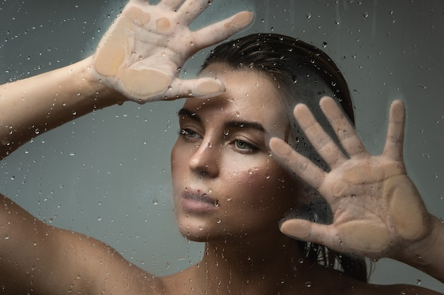 Portret pięknej kobiety uchwyconej przez mokre szkło