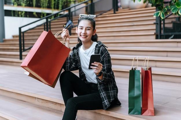 Portret pięknej kobiety umieszcza okulary na głowie trzymając torbę na zakupy