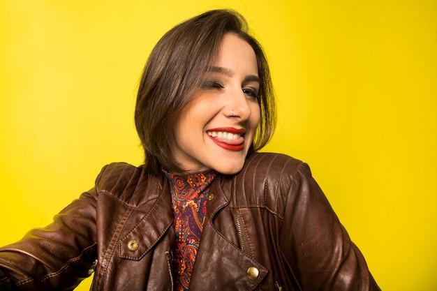 Portret pięknej kobiety uśmiechnięte sukcesy robi selfie na żółtej ścianie