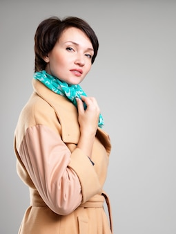 Portret pięknej kobiety w beżowym jesiennym płaszczu z zielonym szalikiem