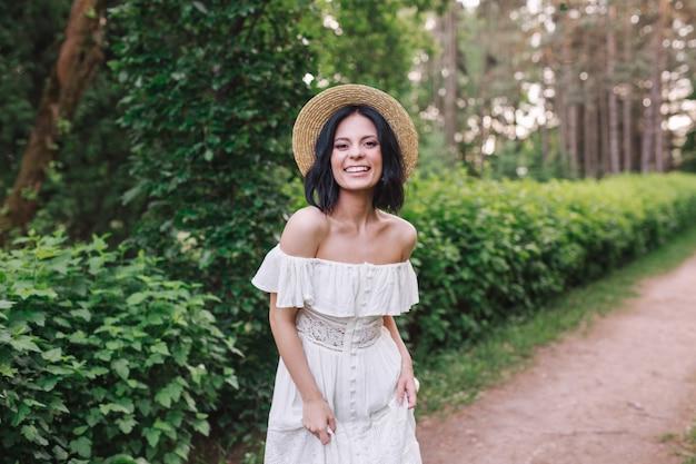 Portret pięknej kobiety w białej sukni vintage i słomkowy kapelusz stojący w parku