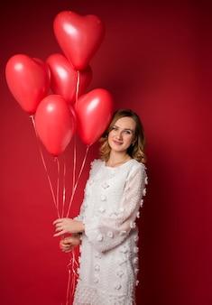 Portret pięknej kobiety w białej sukni z balonami w kształcie serca na czerwono