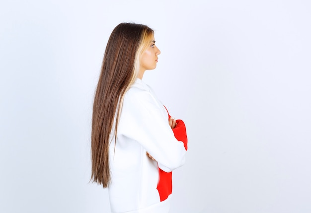 Portret pięknej kobiety w bluzie z kapturem, stojącej i pozującej ze skrzyżowanymi rękami