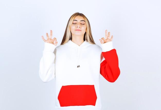 Portret pięknej kobiety w ciepłej bluzie z kapturem, stojącej i medytującej