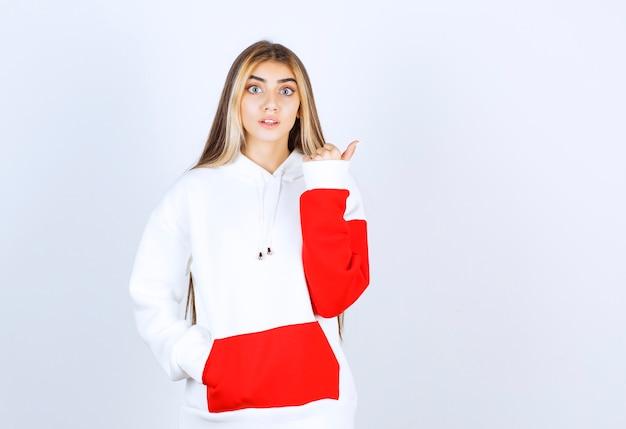 Portret pięknej kobiety w ciepłej bluzie z kapturem, stojącej i patrzącej na kamerę