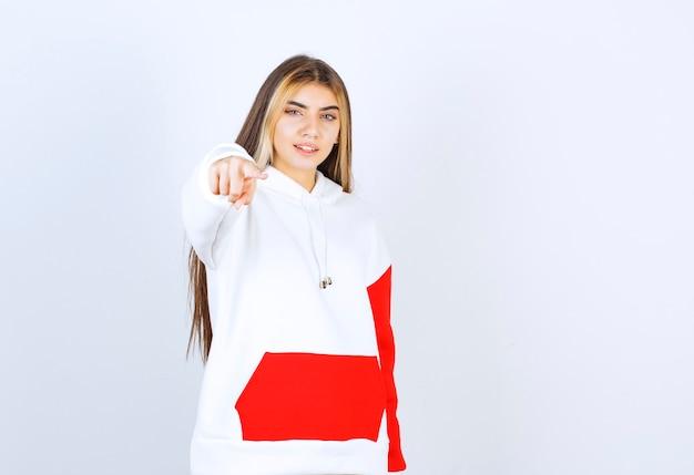 Portret pięknej kobiety w ciepłej bluzie z kapturem, stojącej i wskazującej na kamerę