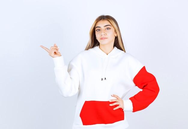 Portret pięknej kobiety w ciepłej bluzie z kapturem, stojącej i wskazującej