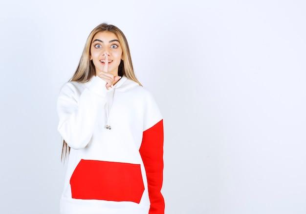 Portret pięknej kobiety w ciepłej bluzie z kapturem, stojącej i wykonującej cichy znak