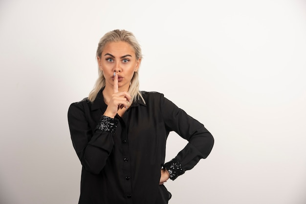 Portret pięknej kobiety w czarnej koszuli pozowanie na białym tle. wysokiej jakości zdjęcie