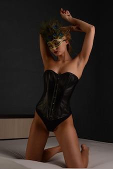 Portret pięknej kobiety w czarnym skórzanym gorsecie i weneckiej masce