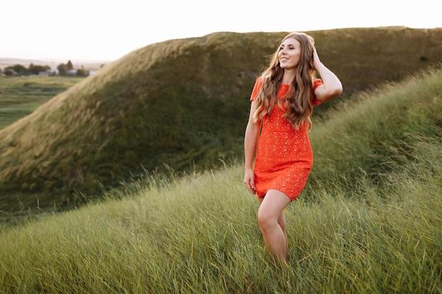 Portret pięknej kobiety w czerwonej sukience w zielonej trawie na polu