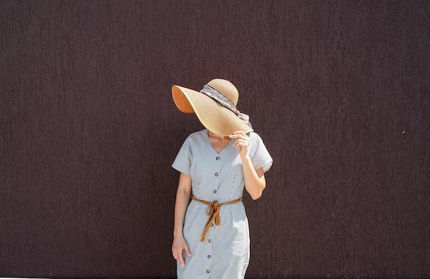 Portret pięknej kobiety w eleganckim letnim kapeluszu na fioletowym tle ściany