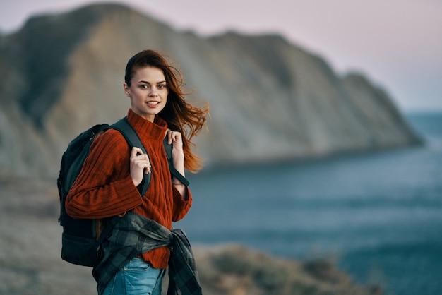 Portret pięknej kobiety w górach blisko morza i plecak na plecach