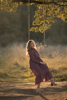 Portret pięknej kobiety w letniej sukience kołyszącej się w lesie