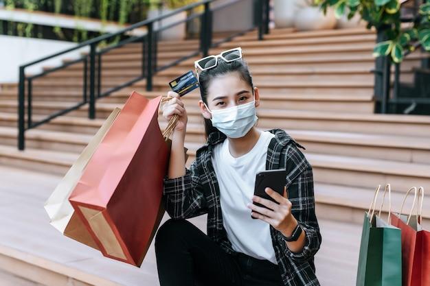 Portret pięknej kobiety w masce i zakładanie okularów na głowę trzymając torbę na zakupy