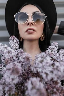 Portret pięknej kobiety w modnych okularach przeciwsłonecznych w eleganckim eleganckim czarnym kapeluszu ze złotymi kolczykami vintage z kwiatami bzu w pobliżu metalicznej szarej ściany w mieście. wspaniała dziewczyna modelka.
