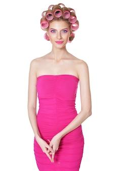 Portret pięknej kobiety w różowej sukience z lokówkami w studio