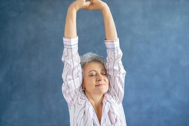 Portret pięknej kobiety w średnim wieku w stylowej piżamie w paski, rozciągającej ciało po przebudzeniu wczesnym rankiem