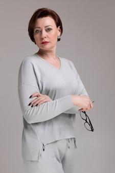 Portret pięknej kobiety w świetle ubrania z okularami w ręku