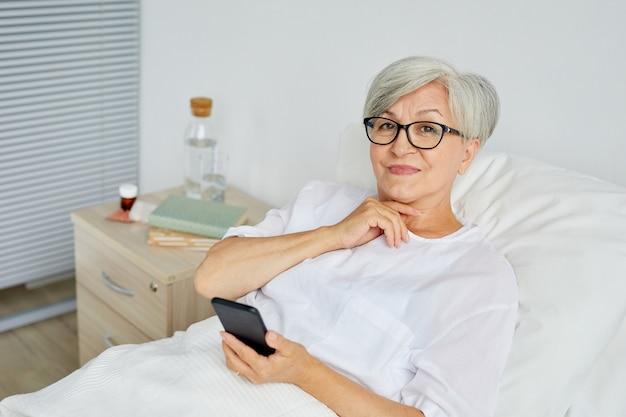 Portret pięknej kobiety w wieku na sobie białe ubrania, leżąc na łóżku na oddziale szpitalnym trzymając smartfon