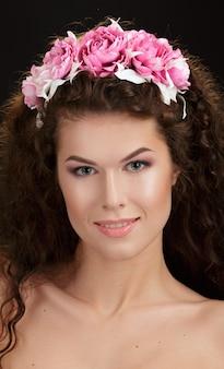 Portret pięknej kobiety wiosna noszenie wieniec kwiatów.